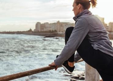 Женщина наклоняется вперед, чтобы размять уставшие мышцы на ногах после пробежки по городу, чтобы предотвратить венозную недостаточность