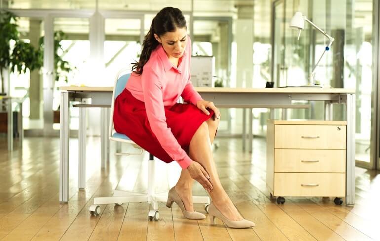 Женщина сидит на стуле в офисе и прикасается к своей ноге