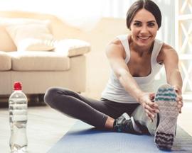 Женщина выполняет гимнастику на коврике для йоги для профилактики тяжести в ногах