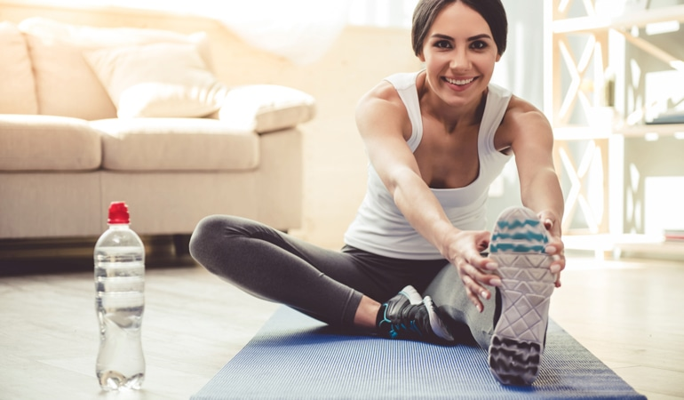 Женщина на коврике для йоги наклоняется вперед, выполняя растяжку мышц ног для профилактики венозной недостаточности.